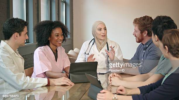 confident muslim doctor meets with healthcare professionals - carers stock photos and pictures