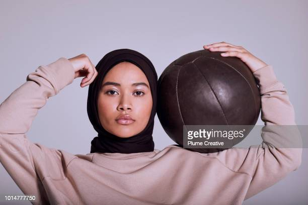 Confident muslim woman with medicine ball