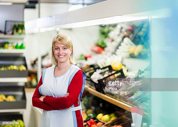 Confident owner standing at convenience store