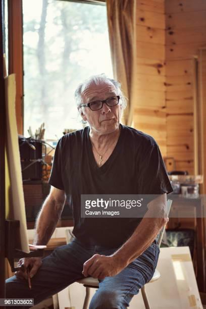 confident painter sitting at workshop - einzelner senior stock-fotos und bilder