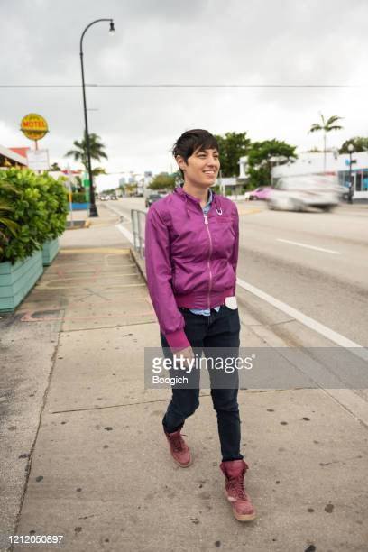 confident person walking outdoors by city street in miami florida - bomber jacket stock pictures, royalty-free photos & images