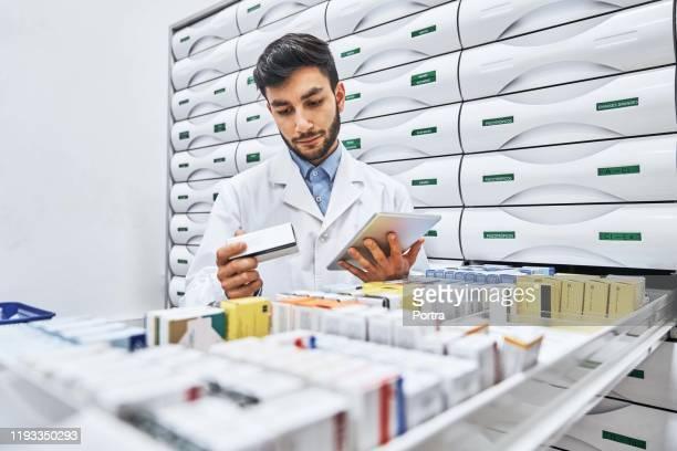 confident pharmacist reading label on merchandise - prescription medicine stock pictures, royalty-free photos & images