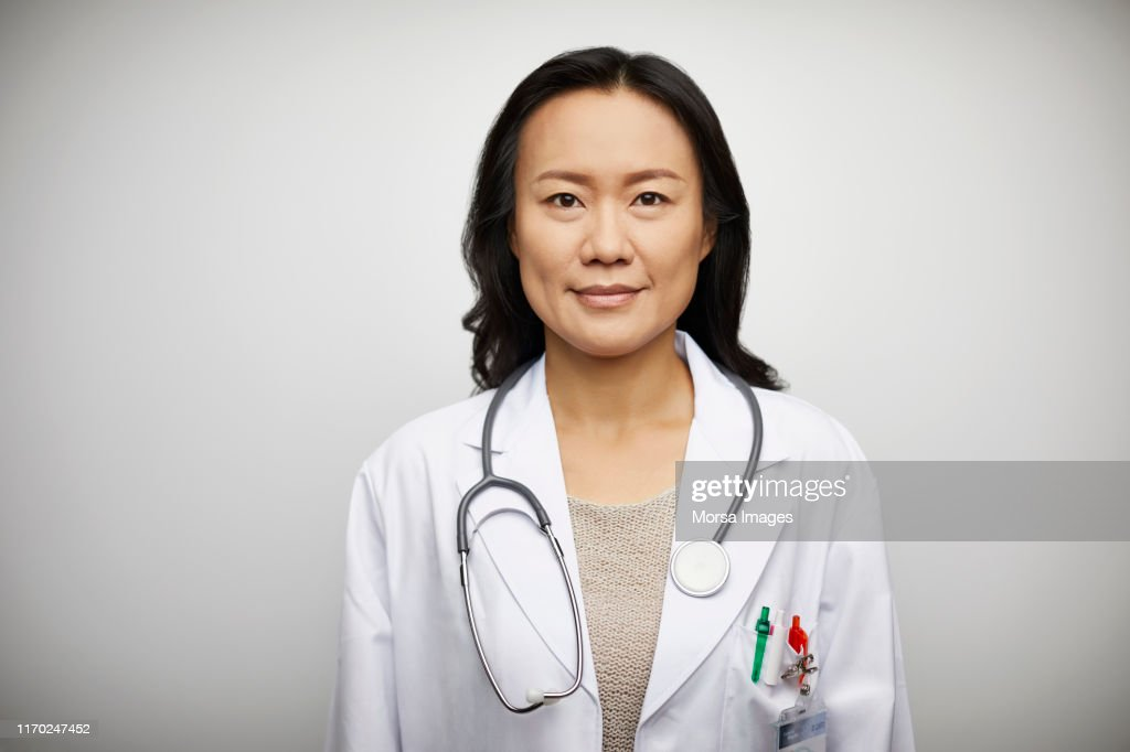 Confident portrait of female doctor in lab coat : Foto de stock