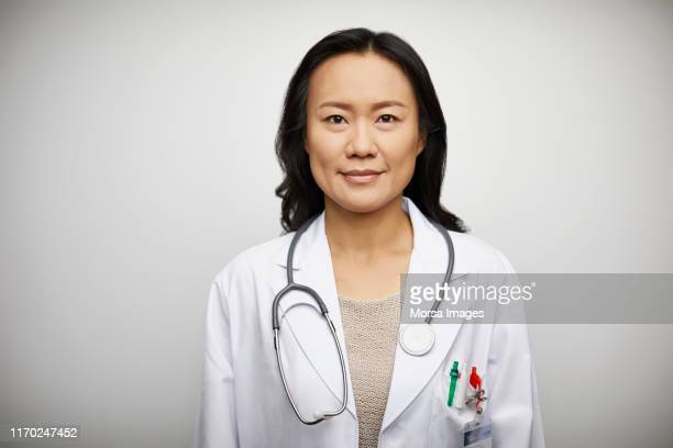 confident portrait of female doctor in lab coat - dokter stockfoto's en -beelden