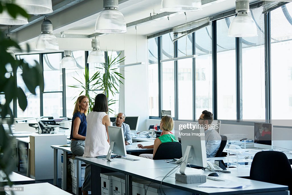 Confident professionals discussing in office : Stock Photo