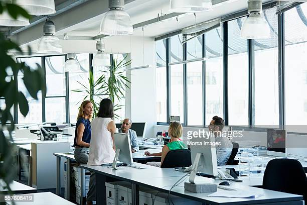 confident professionals discussing in office - werkplek stockfoto's en -beelden