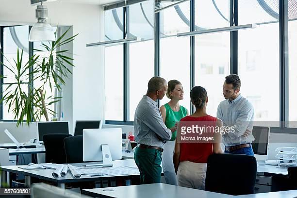 confident professionals discussing in office - cuatro personas fotografías e imágenes de stock