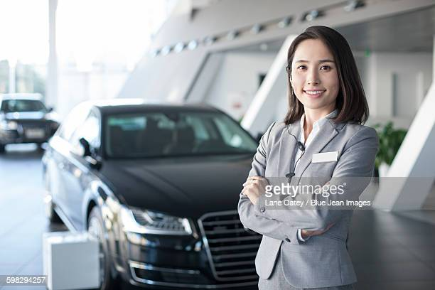 Confident saleswoman standing with new cars in showroom