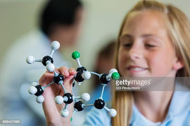 Confident schoolgirl with atomic structure model