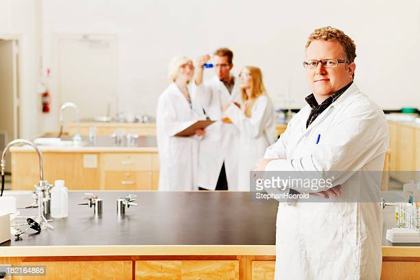 Confident scientist and his team in a laboratory