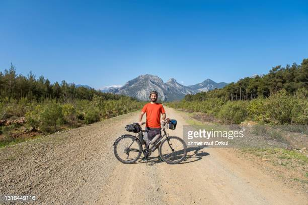 confident, self-confident young 25-30 years old posing with a bicycle on a dirt road - 25 29 years stock pictures, royalty-free photos & images