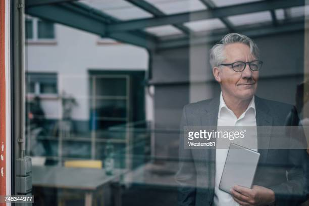 Confident senior businessman behind windowpane