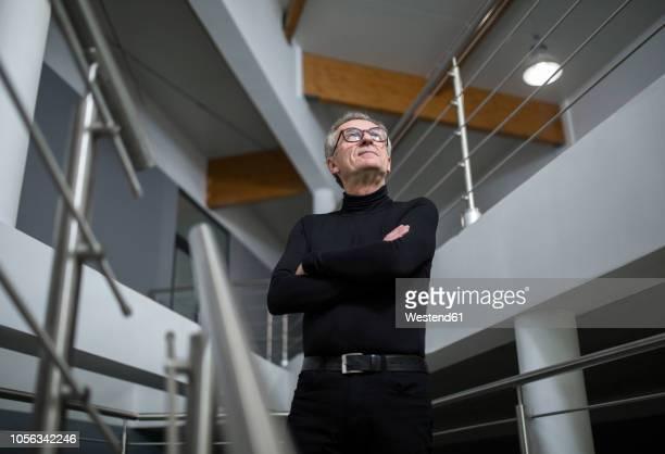 confident senior businessman standing in office hallway - vista de ángulo bajo fotografías e imágenes de stock