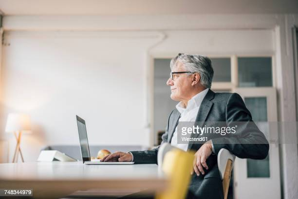 confident senior businessman using laptop - van de zijkant stockfoto's en -beelden