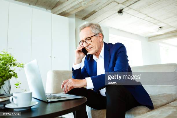 confident senior businessman working on laptop in the office - business men stock pictures, royalty-free photos & images