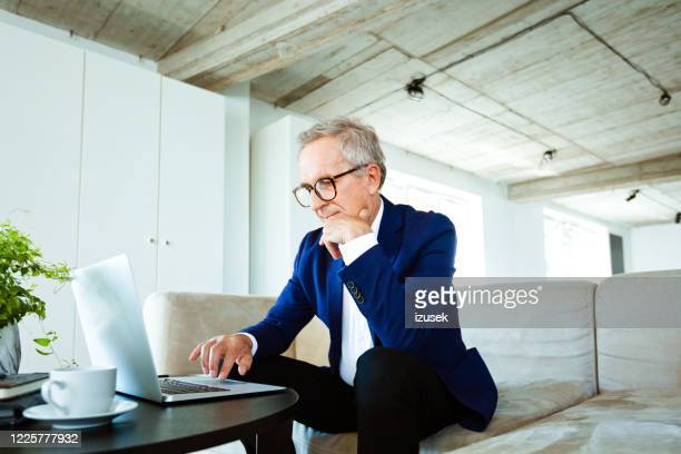 confident senior businessman working on laptop in the office - working stock pictures, royalty-free photos & images