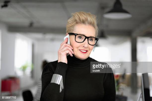 Confident senior businesswoman talking on phone in the office