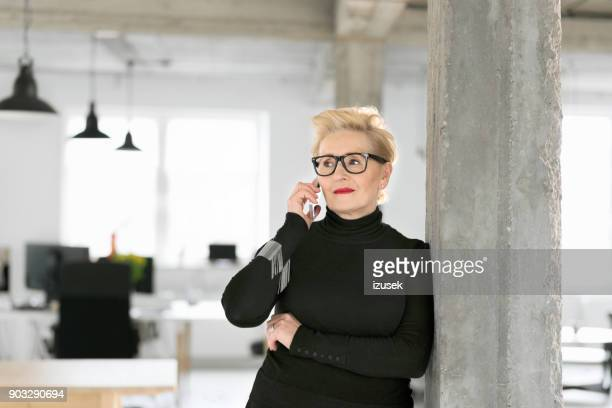 confident senior businesswoman talking on phone in the office - millionnaire stock photos and pictures