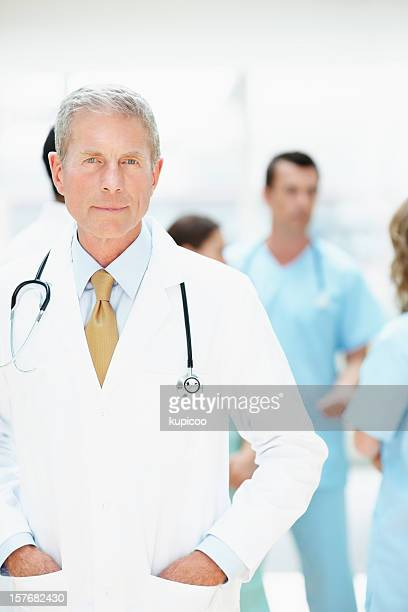 Confident senior doctor with his team in blurry background