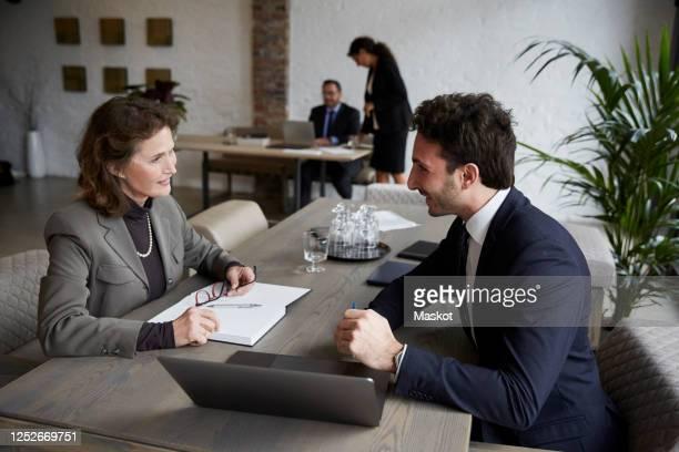 confident senior female lawyer smiling while discussing over laptop with young businessman during meeting at office - finanzen und wirtschaft stock-fotos und bilder