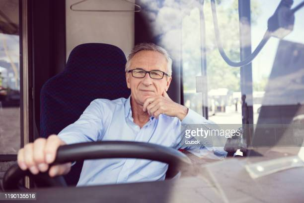 confident senior male driver in bus - confidence stock pictures, royalty-free photos & images