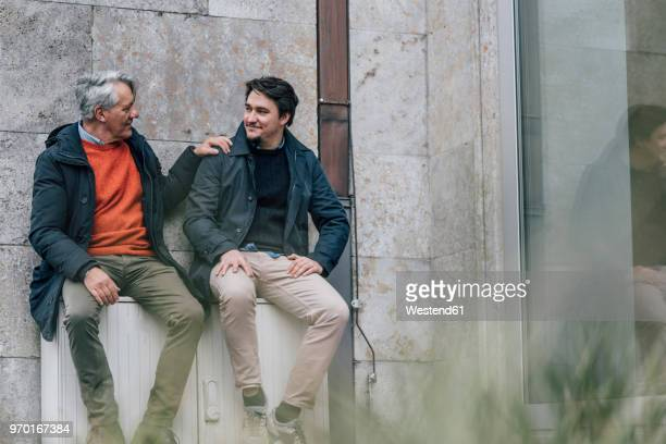 confident senior man and young man sitting in the city talking - vater stock-fotos und bilder