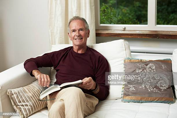 confident senior man reading book on sofa - one man only stock pictures, royalty-free photos & images