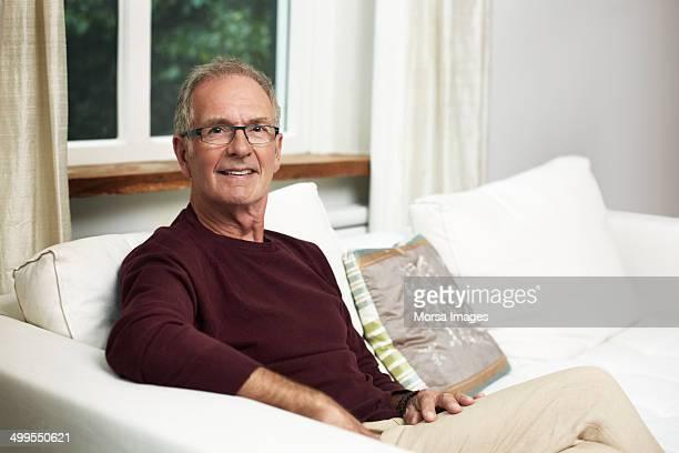 confident senior man sitting on sofa at home - 65 69 ans photos et images de collection