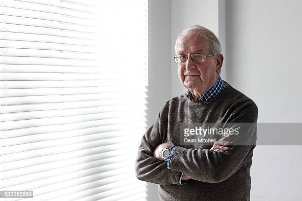 confident senior man standing by a window - only mature men stock pictures, royalty-free photos & images