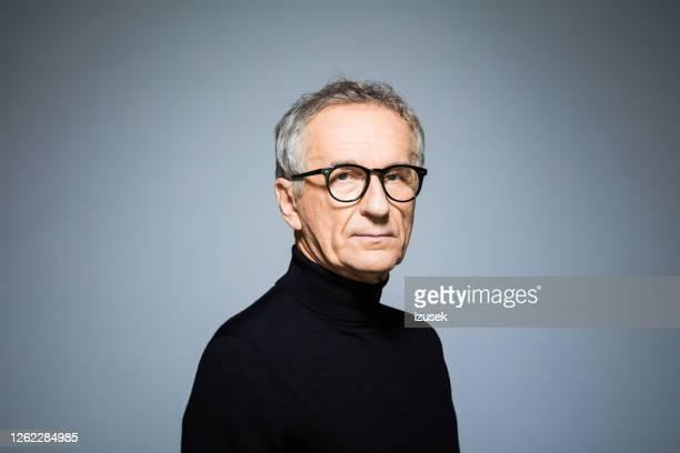 confident senior man wearing black turtleneck - portrait stock pictures, royalty-free photos & images