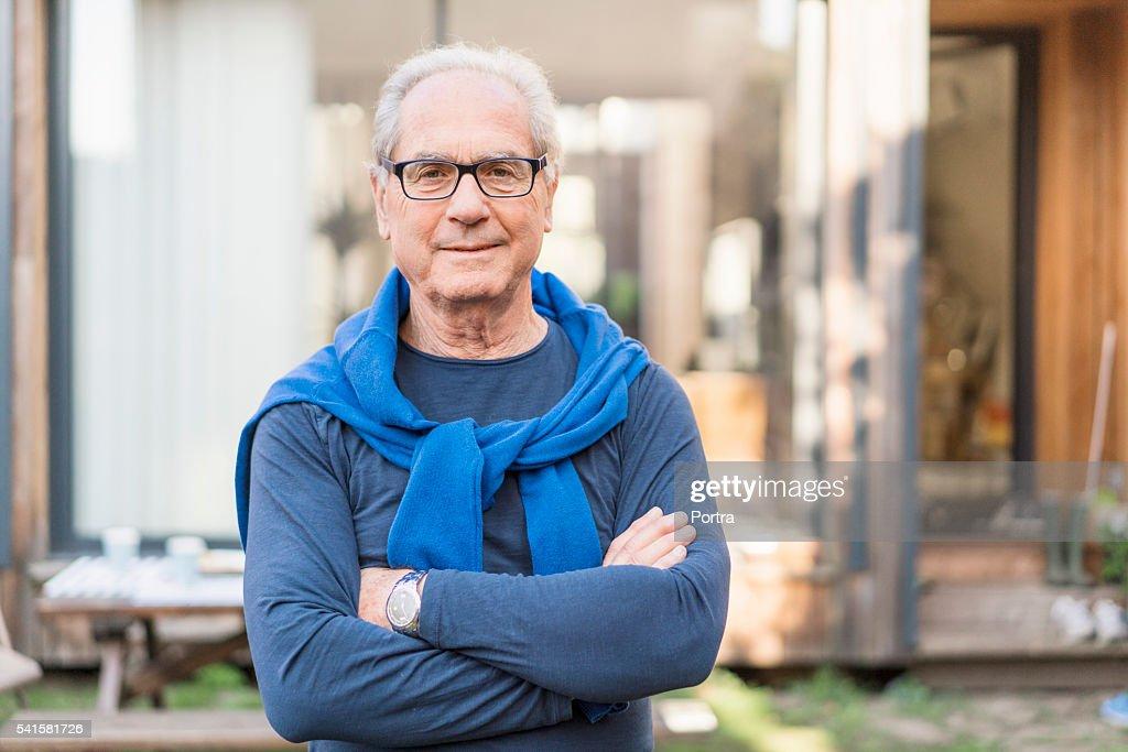 Zuversichtlich Älterer Mann mit Arme verschränkt im Garten : Stock-Foto