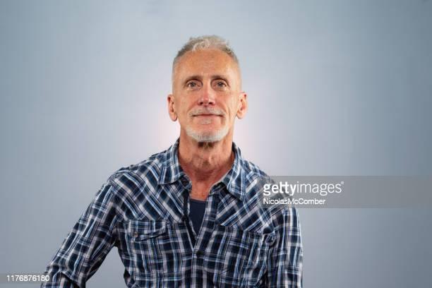 confident senior man with blue plaid shirt studio portrait - plaid shirt stock pictures, royalty-free photos & images