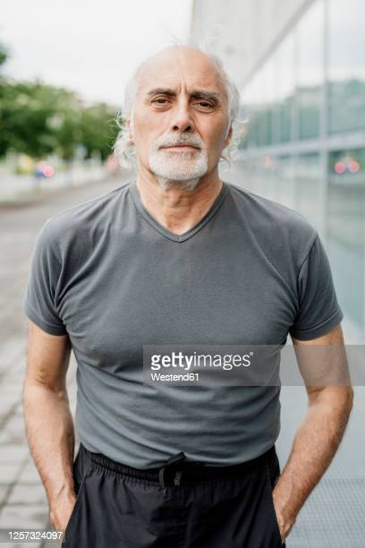 confident senior man with hands in pockets standing in city - hands in pockets stock pictures, royalty-free photos & images