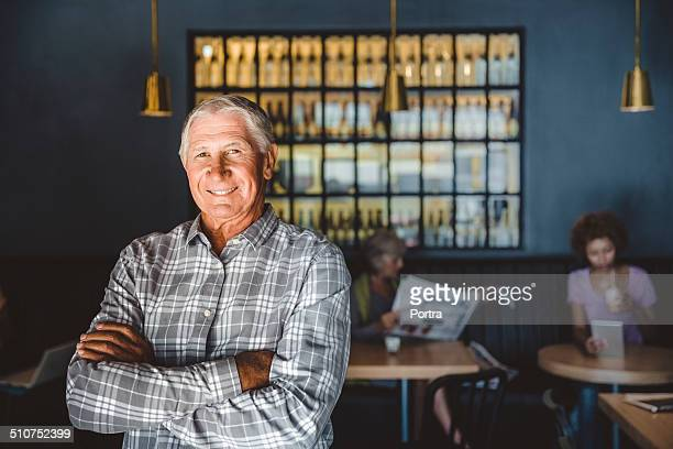 Confident senior owner standing at cafe