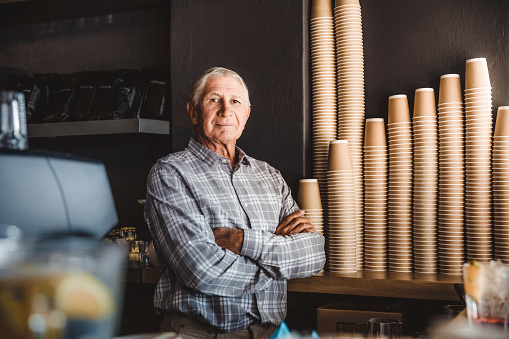 Confident senior owner standing at cafe - gettyimageskorea