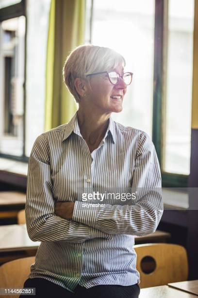 insegnante senior fiducioso con le braccia incrociate in classe. - maestra foto e immagini stock
