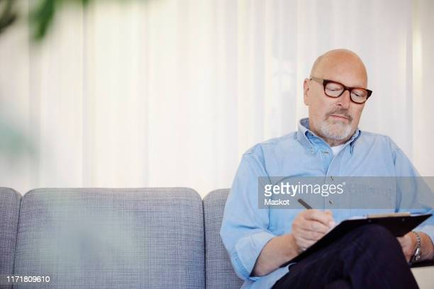 confident senior therapist writing on clipboard at wellness center - mental health professional stock pictures, royalty-free photos & images