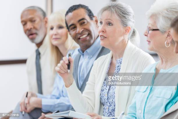 Confident senior woman asks question during seminar