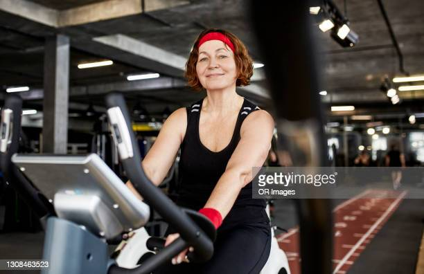 confident senior woman exercising on a stationary bike in gym - headband stock pictures, royalty-free photos & images