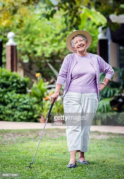 Confident senior woman holding golf club