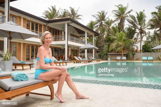 Confident senior woman in bikini sitting on sun lounger by pool