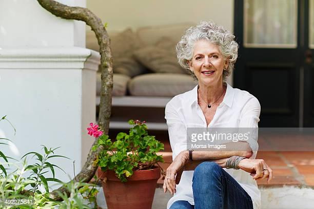 confident senior woman sitting at porch - blouse stock-fotos und bilder