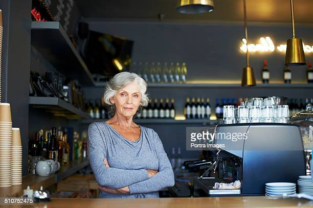 Confident senior woman standing at cafe counter