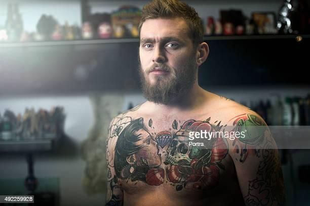 Confident shirtless tattooed man in studio