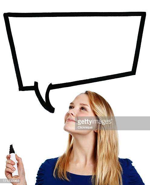 Confident, smiling blonde teenager looks up at hand-drawn speech bubble