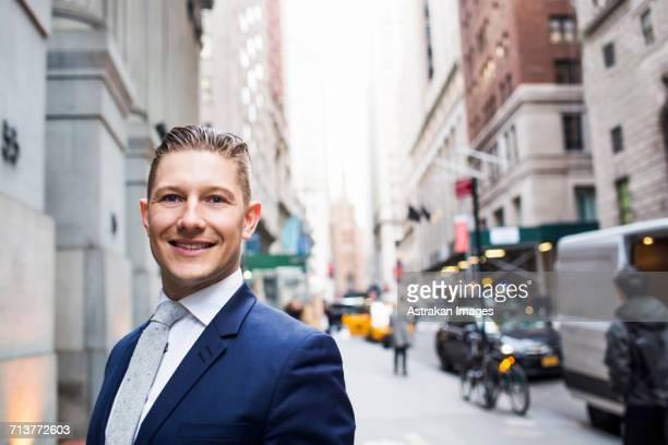 confident smiling businessman standing on sidewalk in city - só um adulto de idade mediana - fotografias e filmes do acervo