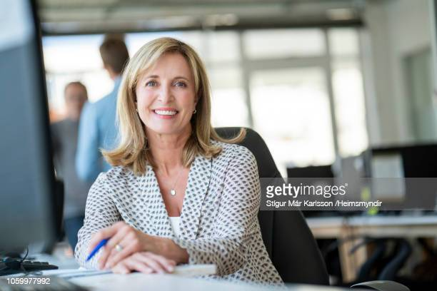confident smiling businesswoman sitting in office - smart casual stock pictures, royalty-free photos & images