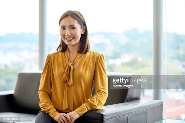 zuversichtlich lächeln geschäftsfrau auf sofa - langärmlig stock-fotos und bilder