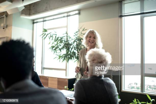 confident smiling businesswoman speaking with colleagues at meeting - small group of people stock pictures, royalty-free photos & images