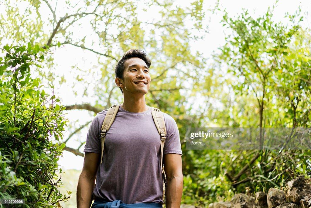 Confident smiling hiker standing against trees : Foto de stock